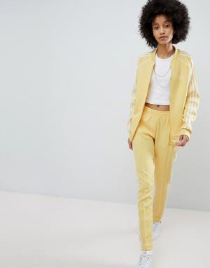 Adidas Originals Желтые спортивные штаны с тремя полосами adicolor. Цвет: желтый