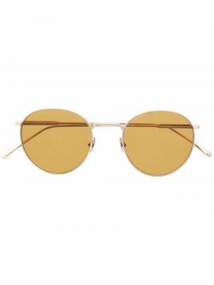 Солнцезащитные очки в круглой оправе Lacoste. Цвет: золотистый