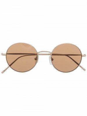 Солнцезащитные очки в круглой оправе DKNY. Цвет: золотистый
